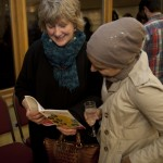Two audience members browse the programme