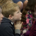 Young boy in audience listening to author