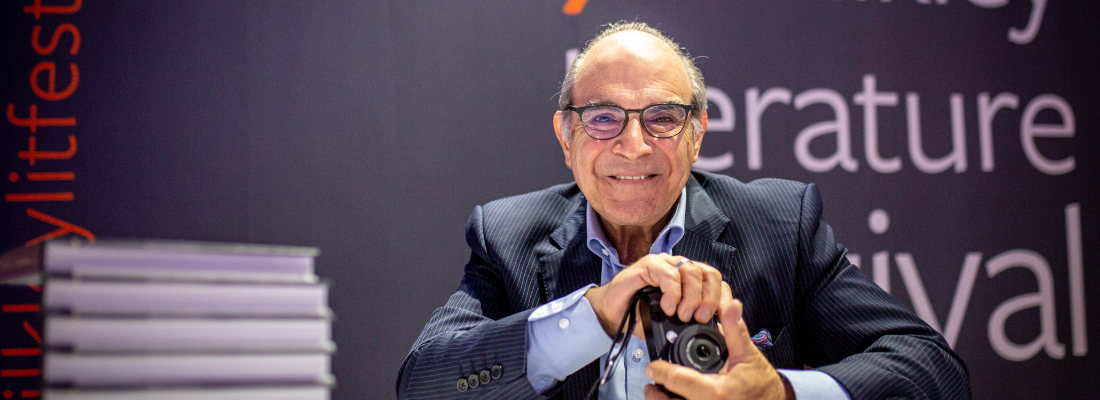 Image of David Suchet smiling, holding a camera, with a pile of books