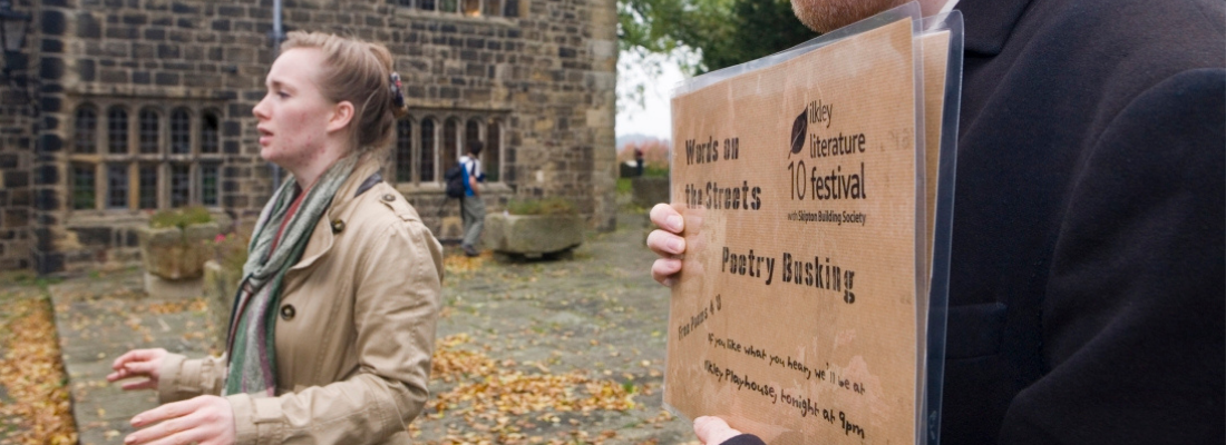 Image of a woman performing in the Ilkley Manor House Courtyard, and a person holding a sign on a brown piece of paper.