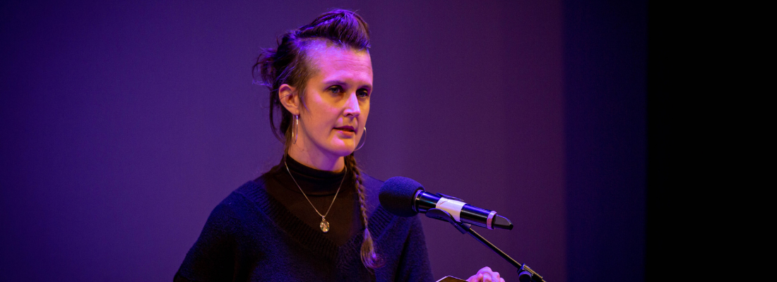 Image of woman in a black top stood speaking into a microphone