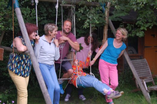 Image of five people by a swingset, smiling and looking at each other.