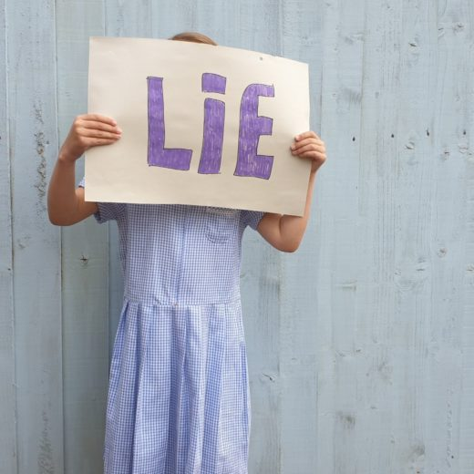 Image of young child holding a sign that reads 'Lie' in front of her face, against a white background.